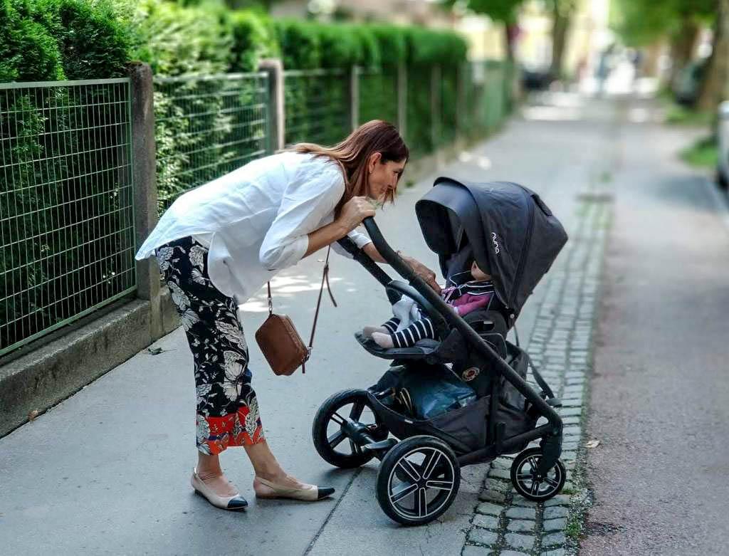 Frau beugt sich über Kinderwagen Nuna Mixx