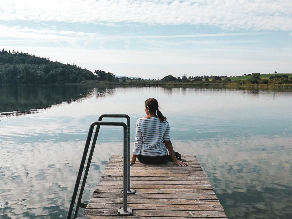 Frau sitzt an einem See